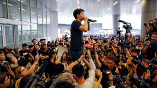 El activista Joshua Wong se dirige a la prensa y a un grupo de seguidores frente al Consejo Legislativo de Hong Kong el 17 de junio de 2019.