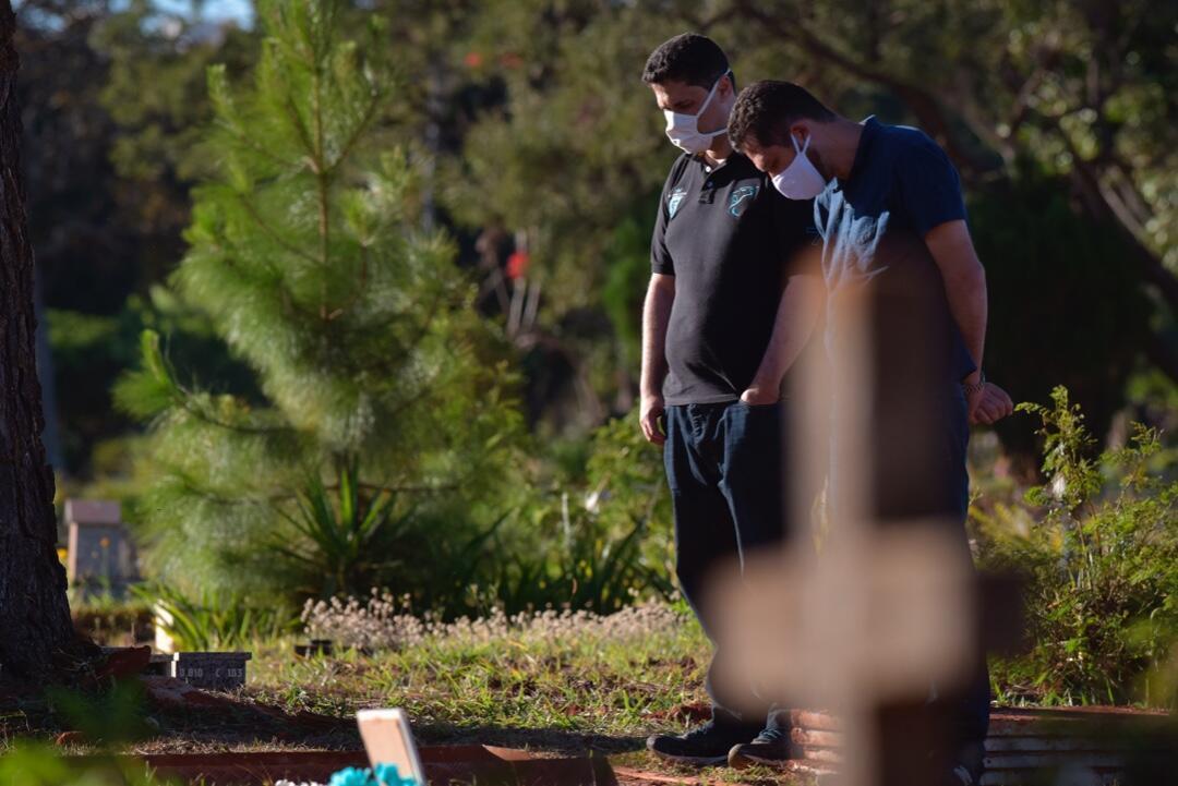 Dos ciudadanos brasileños asisten en solitario al funeral de un ser querido fallecido por Covid-19 en Brasilia, Brasil.
