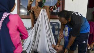 Dos personas pesan a un niño antes de administrarle vacunas contra la polio y la tuberculosis en Banda Aceh, Indonesia, el 11 de agosto de 2020