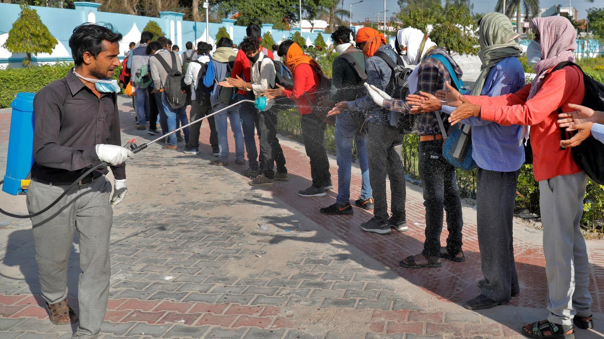 Archivo-Un trabajador municipal rocía desinfectante sobre los trabajadores migrantes antes de que aborden un autobús para regresar a sus aldeas, durante un cierre nacional de 21 días para frenar la propagación de la enfermedad por coronavirus (COVID-19), en Lucknow, India, 30 de marzo de 2020.