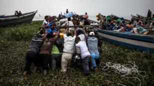 Des déplacés internes congolais poussent une embarcation pour traverser le lac Albert, près de Bunia en Ituri, et rejoindre l'Ouganda voisin.