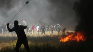Un manifestante palestino utiliza una cuerda para arrojar piedras durante los enfrentamientos contra las tropas israelíes en la frontera entre Israel y Gaza, en una protesta en la que los palestinos exigen el derecho a regresar a su patria, en el sur de la Franja de Gaza, el 6 de abril de 2018.