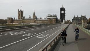 Archivo: ciclistas montan sobre el puente de Westminster casi vacío, mientras continúa la propagación de la enfermedad por coronavirus. Londres, Reino Unido, el 8 de abril de 2020.