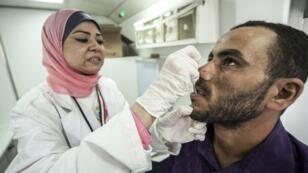 Un médecin égyptien prend un échantillon de salive pour détecter l'hépatite C chez un patient.