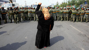 Una mujer grita a la policía paramilitar china mientras una multitud de lugareños enfurecidos se enfrentan a las fuerzas de seguridad en una calle en Urumqi, capital de Xinjiang, durante una protestas en 2009.