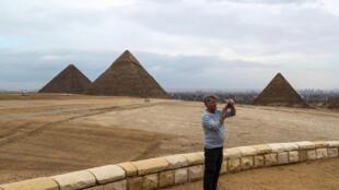 Un turista saca fotos con su teléfono móvil junto a las pirámides de Giza, el 13 de marzo de 2020 al suroeste de El Cairo