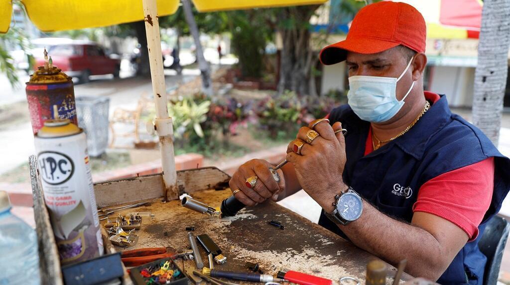 IMAGEN Marcel, reparador de fosforeras, trabaja en una calle el 3 de marzo de 2021, en La Habana (Cuba).