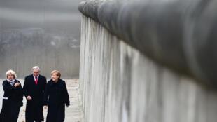 Angela Merkel longe une portion du mur de Berlin en compagnie de la ministre allemande de la Culture, Monika Gruetters, et du maire de Berlin, Klaus Wowereit.