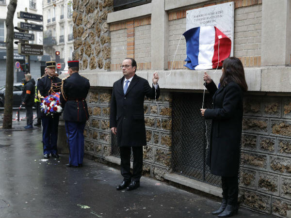 French President François Hollande and Paris Mayor Anne Hidalgo unveil a commemorative plaque near La Belle Equipe café, on the first anniversary of the Paris terror attacks.