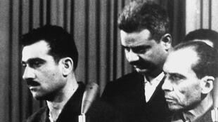 صورة تعود لـ9 أيار/مايو 1965، تظهر الجاسوس الإسرائيلي إيلي كوهين (يسار) ومتهمين آخرين (لم يتم التعرف عليهما)، أثناء محاكمتهم في دمشق، قبل عشرة أيام من إعدام كوهين.