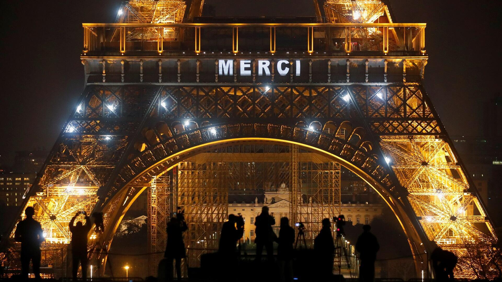 برج إيفل بالعاصمة الفرنسية باريس يضاء بكلمة شكرا تعبيرا عن الامتنان للعاملين في قطاع الصحة لدورهم في مكافحة وباء كورونا، 27 مارس/آذار 2020.