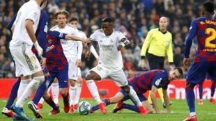 مهاجم ريال مدريد فينيسيوس وسط دفاع برشلونة قبل أن يسجل الهدف الأول في الكلاسيكو، 1 مارس/آذار 2020.
