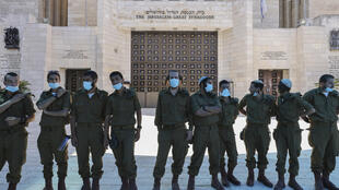 Israeli soldiers wearing masks to avoid the spread of the novel coronavirus stand outside the Jerusalem Great Synagogue, which will be closed for the Jewish New Year for the first time due to the pandemic