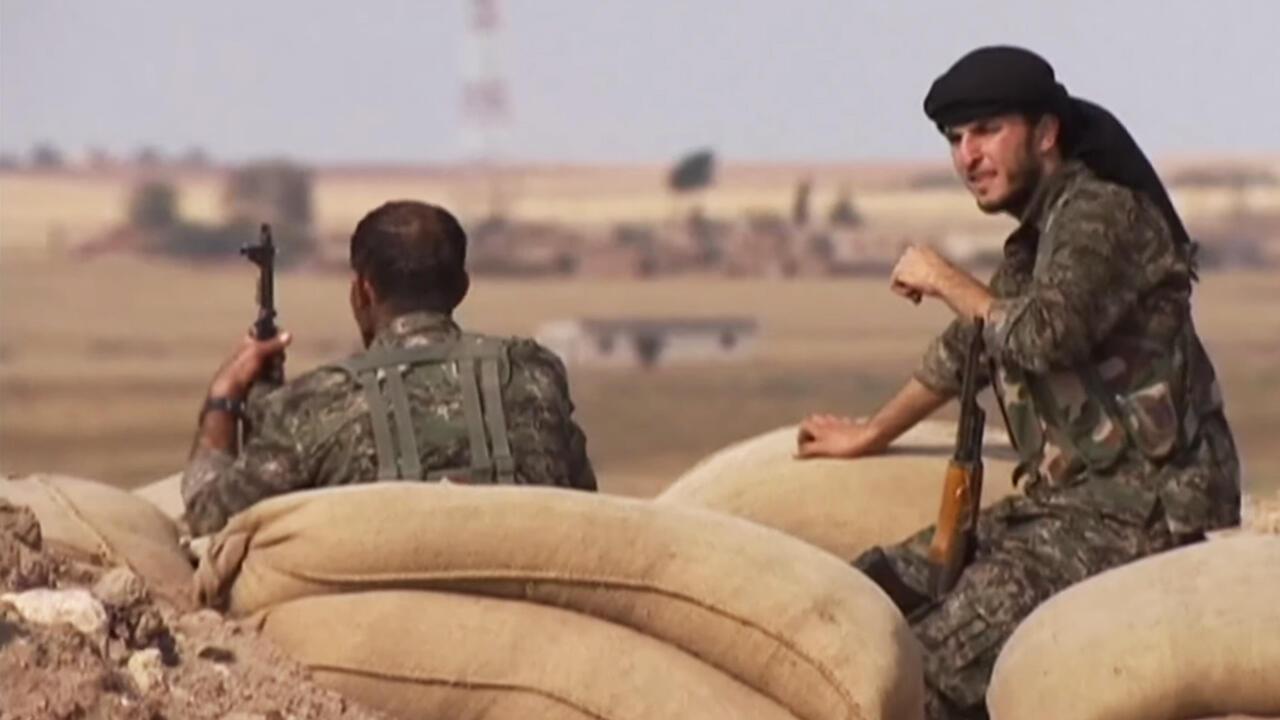 Una bandera de los grupos kurdos mientras ondea en una zona de tensión en medio del territorio sirio.
