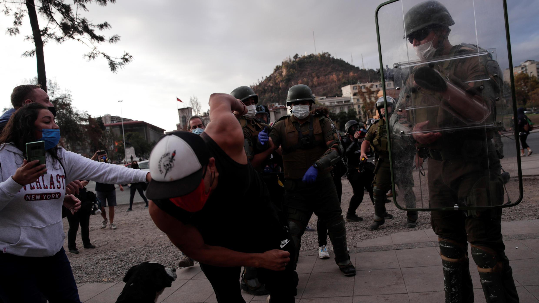 Policías se enfrentan a manifestantes, este 27 de abril, durante las protestas contra el Gobierno de Sebastián Piñera y por la celebración del día del Carabinero, en la céntrica Plaza Italia, epicentro de las protestas en el país desde el pasado 18 de octubre de 2019, en Santiago (Chile).