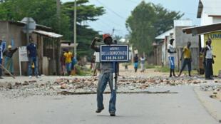 """Un manifestant opposé à un troisième mandat du président Pierre Nkurunziza tient une pancarte sur laquelle est écrit """"avenue de la démocratie"""", le 26 mai 2015, à Bujumbura."""