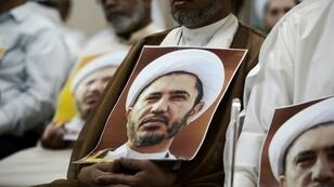 A Bahraini man holds a picture of Sheikh Ali Salman, head of the Shiite opposition movement Al-Wefaq, during a protest on May 29, 2016 against his arrest