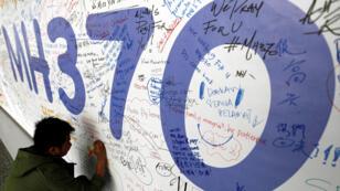 Un hombre escribe un mensaje dedicado para los pasajeros desaparecidos del avión MH370 de Malaysia Airlines, en el Aeropuerto Internacional de Kuala Lumpur, Malasia, 13 de marzo de 2014.