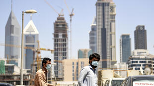 Foreign workers clad in masks to protect against coronavirus push bicycles along a street in the Satwa district of Dubai