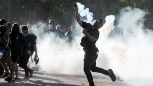 Una manifestante arroja un bote de humo contra la policía en Santiago de Chile, el 21 de octubre de 2019.