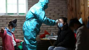 عامل طبي يرتدي بدلة واقية يقيس درجة حرارة جسم فتاة، في مقاطعة دانزيهاي، كياندونغنان مياو ودونغ ذاتية الحكم، الصين، 31 يناير/ كانون الثاني 2020.