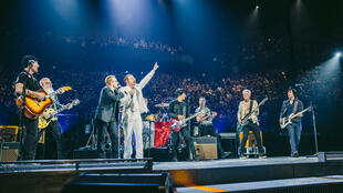 Bono, le chanteur du groupe U2, avec Jesse Hughes (en blanc), chanteur des Eagles of Death Metal lors d'un concert à Paris, le 7 décembre 2015.