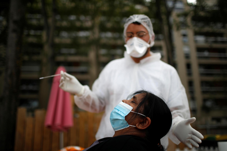 Un trabajador de la salud, vestido con un traje protector y una mascarilla, se prepara para administrar un hisopo nasal a un paciente en un sitio de prueba para la enfermedad por coronavirus instalado en el Bassin de la Villette en París, Francia, el 25 de agosto 2020.