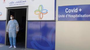 طبيب طوارئ تونسي في مدخل قسم خاص بمرضى كوفيد في مستشفى عبد الرحمن مامي في ولاية أريانة قرب العاصمة تونس بتاريخ 12 آذار/مارس 2021