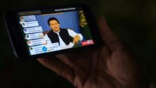 باكستاني يتابع عبر هاتفه المحمول أول خطاب لرئيس الوزراء الجديد عمران خان في كراتشي في 19 آب/أغسطس 2019.
