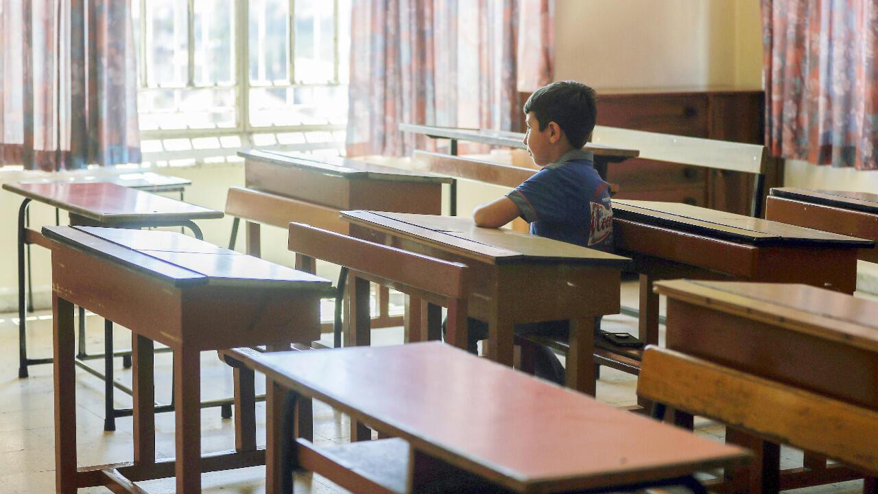 """Un élève libanais assis dans sa classe vide après être venu récupérer les livres qu'il avait laissés avant le confinement de Covid-19, à l'école """"Notre-Dame-de-Lourdes"""" dans la ville de Zahle, le 30 juin 2020."""