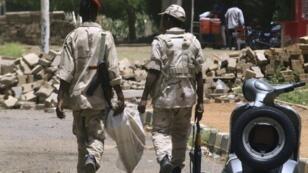 عنصران من قوات الدعم السريع خلال دورية في شارع النيل في الخرطوم