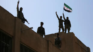 Turkish-backed Syrian fighters wave the Syrian opposition flag on top of a building in the southwestern neighbourhoods of the border town of Tal Abyad on October 13, 2019.