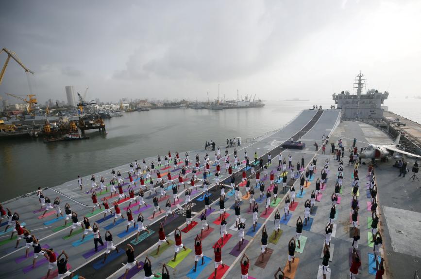 Miembros de la Marina de India practican yoga en una pista aérea en Bombay, India.