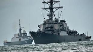 Le destroyer USS John S. McCain (à droite) dont la coque est endommagée à bâbord est remorqué par la marine singapourienne.