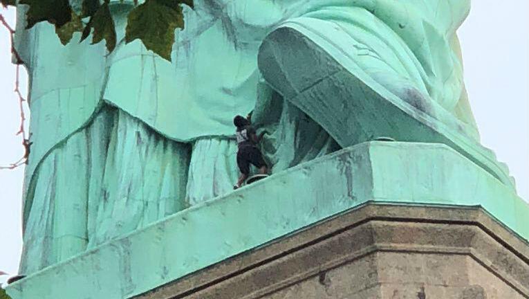 El personal de emergencia ve una manifestante subir a la base de la Estatua de la Libertad en Nueva York.