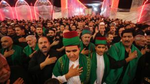 Peregrinos chiitas participan en una ceremonia en el santuario del Imam Husáin en la ciudad iraquí de Karbala, al sur del país, el 19 de septiembre de 2018, en vísperas del décimo día del luto de Muharram, que marca la cima de la Ashura.
