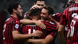 AC Milan's Ismael Bennacer (2nd L)  celebrates with Hakan Calhanoglu (C) after scoring against Bologna.