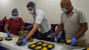 Moldovan tennis player Dmitrii Baskov (C) has been helping feed poor people in India during the national lockdown