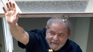 Depuis le siège du Parti des travailleurs, à Sao Paulo, Luiz Inacio Lula da Silva fait signe aux personnes venues le soutenir alors qu'il devait être interrogé par les enquêteurs de l'affaire Petrobras le 4 mars 2016.