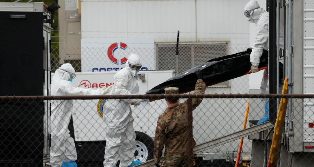 Trabajadores con un equipo de protección personal mueven el cuerpo de un fallecido fuera del Hospital Universitario en Newark, Estados Unidos, el 6 de mayo de 2020.