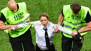 Une des membres des Pussy Riot est escortée en dehors du terrain, lors de la finale du mondial, le 15 juillet 2018.