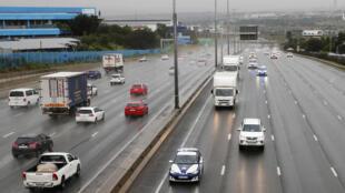 Des véhicules de la police sud-africaine escortent deux camions réfrigérés transportant des vaccins AstraZeneca/Oxford arrivés à l'aéroport, le 1er février 2021 à Johannesbourg, pour la première vague de vaccination anti-Covid dans le pays