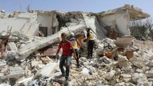 Un civile et des membres de la Défense civile syrienne, connue sous le nom de Casques blancs, vérifient les décombres d'une frappe aérienne à Maaret al-Noman, dans la province d'Idleb, le 30 mai 2019.