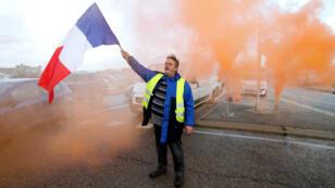 """Un """"Gilet jaune"""" tient à bout de bras un drapeau français lors d'un blocage de l'accès à la raffinerie de Fos-sur-Mer (Bouches-du-Rhône), le 22 novembre 2018."""