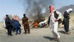 Des Pakistanais se sont rassemblés le 21 mai 2016 autour de la carcasse d'une voiture touchée par une frappe de drone visant le mollah Mansour, le chef des Taliban.
