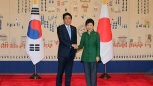 رئيس وزراء اليابان شينزو ابي مصافحا رئيسة كورية الجنوبية بارك غوين-هيه،  تشرين الثاني/نوفمبر 2015
