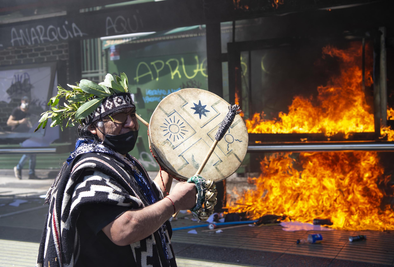 Un indígena mapuche toca una pandereta en medio de enfrentamiento entre manifestantes y la policía antidisturbios durante una protesta en el marco del Día de la Raza, el 12 de octubre de 2020 en Santiago.