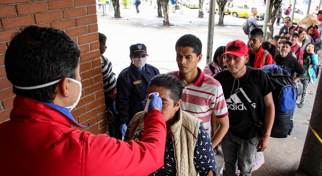 Un funcionario de salud ecuatoriano toma la temperatura de ciudadanos colombianos que intentan cruzar el Puente Internacional Rumichaca, dese Ecuador hacia Colombia, el 17 de marzo de 2020.