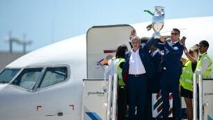 Le selectionneur portugais Fernando Santos brandit la coupe à l'aéroport de Lisbonne, le 11 juillet.