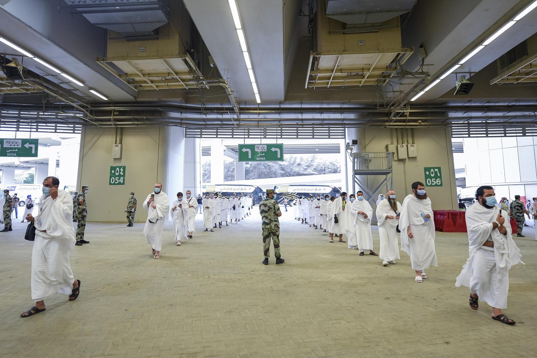 Des hommes aussi observent le dernier rite hajj annuel et s'apprêtent à jeter des pierres sur un mur de lapidation et le deuxième jour de l'Aïd al-Adha, à Mina, près de la ville sainte de La Mecque, en Arabie saoudite, vendredi juillet 31 janvier 2020. La pandémie mondiale de coronavirus a jeté une ombre sur chaque aspect du pèlerinage de cette année, qui a attiré l'année dernière 2,5 millions de musulmans du monde entier vers le mont Arafat, où le prophète Mahomet a prononcé son dernier sermon il y a près de 1400 ans. Seul un nombre très limité de pèlerins a été autorisé à participer au hajj au milieu de nombreuses restrictions visant à limiter la propagation potentielle du coronavirus.